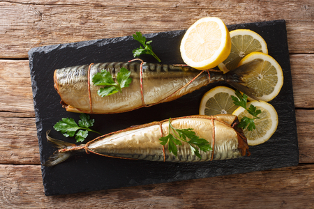Smoked mackerel with lemons and parsley closeup on a black slate board on the table. Horizontal top view from above