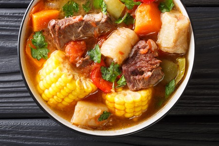 Latin American Sancocho thick meat soup with vegetables close-up on a plate on the table. Horizontal top view from above, rustic style