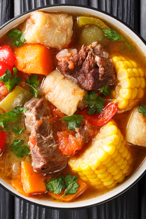 Sancocho Recipe a hearty and absolutely delicious stew made with meat, vegetables and spice close-up on a plate on the table. Vertical top view from above