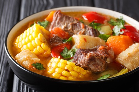 Latin American Sancocho thick meat soup with vegetables close-up on a plate on the table. horizontal, rustic style