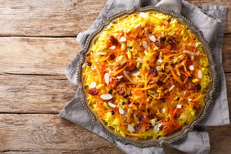 Javaher Polow (jeweled rice) is a traditional Persian rice dish closeup on a plate on the table. horizontal top view from above