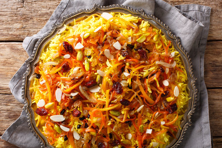 Saffron pilaf with dried fruits, carrots, orange zest, spices and nuts closeup on a plate on the table. horizontal top view from above