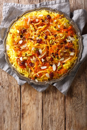 Javaher Polow (jeweled rice) is a traditional Persian rice dish closeup on a plate on the table. Vertical top view from above