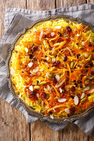 Saffron pilaf with dried fruits, carrots, orange zest, spices and nuts closeup on a plate on the table. Vertical top view from above