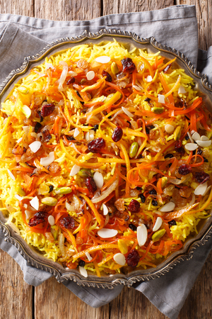 Persian delicious pilaf Javaher Polow (jeweled rice) with dried fruits, carrots, orange zest and nuts closeup on a plate on the table. Vertical top view from above Banco de Imagens