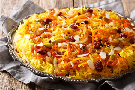 Persian delicious pilaf Javaher Polow (jeweled rice) with dried fruits, carrots, orange zest and nuts closeup on a plate on the table. horizontal