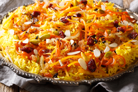 Persian vegetarian festive Javaher Polow (jeweled rice) with dried fruits, carrots, orange zest and nuts closeup on a plate on the table. horizontal