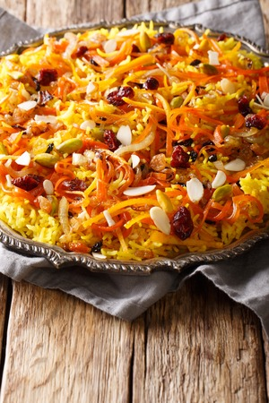 Iranian jeweled rice with dried fruits, carrots, orange zest and nuts closeup on a plate on the table. vertical