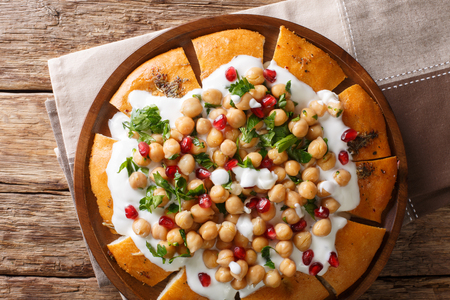 authentic Lebanese Fatteh?is made with yogurt, chickpeas and pita bread close-up on a plate on the table. horizontal top view from above
