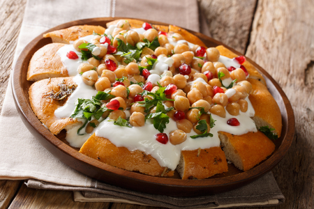 Vegetarian food from pita with chickpeas, yogurt and pomegranate seeds close-up on a plate on the table. horizontal