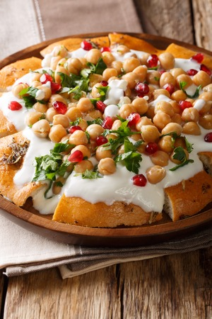 Middle Eastern pita with chickpeas, yogurt and pomegranate seeds close-up on a plate on the table. vertical