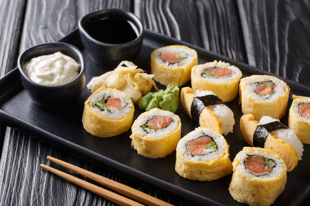 Delicious breakfast Tamagoyaki set sushi roll with rice, omelette, cheese, salmon and avocado close-up with sauces, wasabi and ginger on a plate on the table. horizontal Imagens
