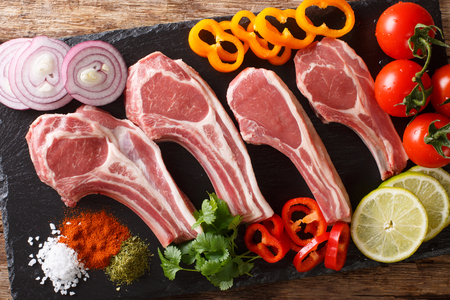 Fresh raw lamb chops on the bone with vegetable ingredients close-up on the table. Horizontal top view from above