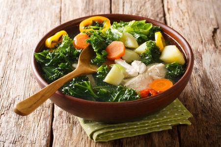 Easy vegetable soup recipe with kale and chicken close-up in a bowl on the table. horizontal