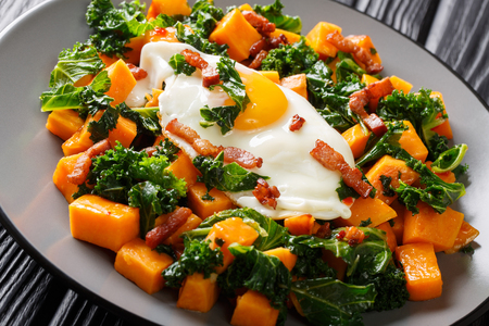 Healthy food sweet potato with kale, bacon and fried egg close-up on a plate on the table. horizontal