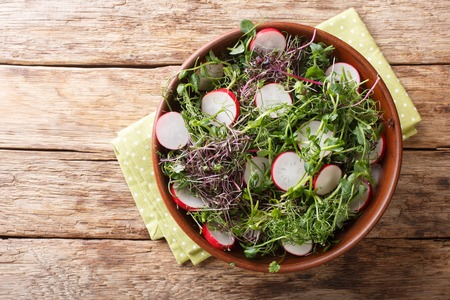 Spring salad of radish with microgreen mix close-up in a bowl on the table. horizontal top view from above Reklamní fotografie