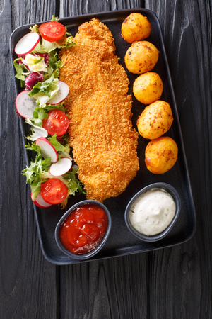 main course of cod fillet in breading with a garnish of new potatoes and fresh vegetable salad close-up on a plate on the table. Vertical top view from above
