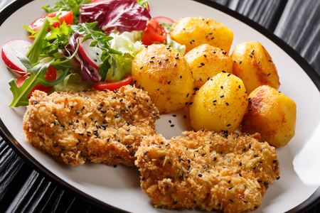 Serve fried steaks in sesame breading with new potatoes and fresh salad close-up on a plate on the table. horizontal