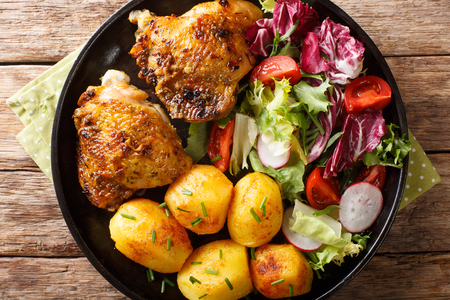 Baked chicken thighs with a garnish of new potatoes and fresh salad close-up on a plate on the table. horizontal top view from above