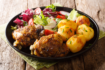 Portion of chicken thighs with new potatoes and fresh salad close-up on a plate on the table. horizontal
