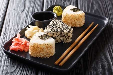 Triangular onigiri with sesame served with ginger, wasabi and soy sauce close-up on a plate on the table. horizontal