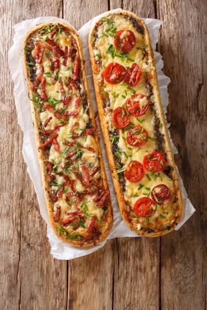 Sandwichs chauds au bacon, champignons, tomates et fromage en gros plan sur du parchemin sur la table. Vue verticale de dessus d'en haut