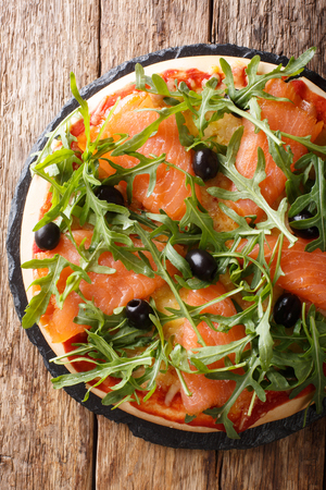 Delicious pizza with salted salmon, arugula, olives and cheese closeup on the table. Vertical top view from above