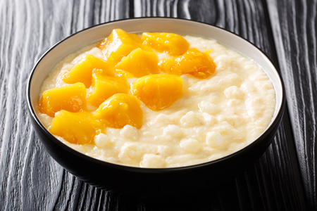 Delicious tapioca vanilla pudding with coconut milk and mango close-up in a bowl on the table. horizontal
