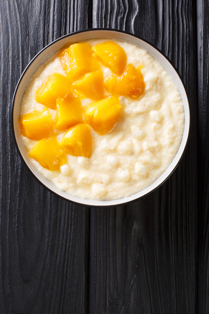 Sweet tapioca pudding with coconut milk and fresh mango close-up in a bowl on the table. Vertical top view from above