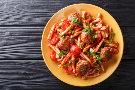 Pasta Casarecce recipe with meat balls, herbs and cheese in tomato sauce closeup on a plate on the table. horizontal top view from above