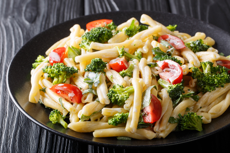 Dietary pasta Casarecce with vegetables dressed with creamy cheese sauce close-up on a plate on the table. horizontal