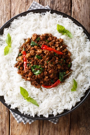 Stir fry basil chicken with chili pepper and soy sauce with a side dish of rice close-up on a plate on the table. Vertical top view from above