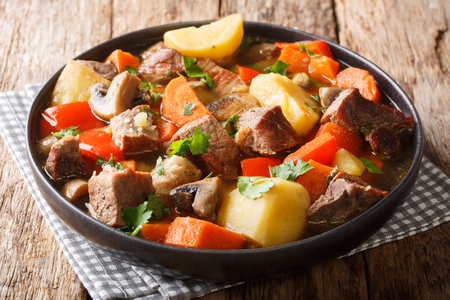Homemade pork stew with seasonal vegetables closeup on a plate on the table. horizontal