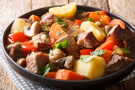 ragout of pork with mushrooms and vegetables close-up on a plate on the table. horizontal Stock Photo