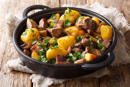 Comida sencilla y abundante de patatas fritas con primer plano de carne de cerdo y setas en una sartén sobre la mesa. horizontal