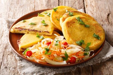La ricetta vegetariana saporita delle pupusas è servita con il primo piano di curtido su un piatto sulla tavola. orizzontale Archivio Fotografico