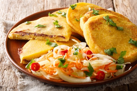 Delicious vegetarian fried Pupusas served with coleslaw close-up on a plate on the table. horizontal Zdjęcie Seryjne