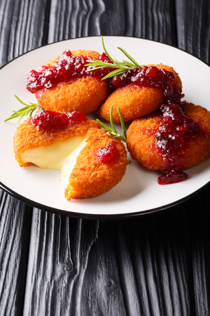 Hot Camembert cheese in breading served with cranberry sauce and rosemary closeup on a plate on the table. vertical