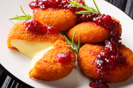 Baked Camembert breaded with cranberry sauce close-up on a plate on the table. horizontal