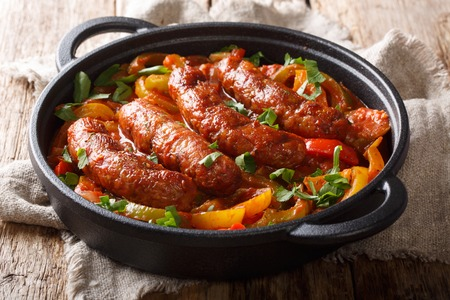 Grilled homemade sausages with colored peppers, onions, herbs and tomatoes closeup in a frying pan on the table. horizontal Banque d'images