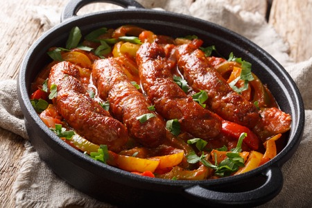 Italian food grilled sausage with grilled peppers, onions, herbs and tomatoes closeup in a frying pan on the table. horizontal