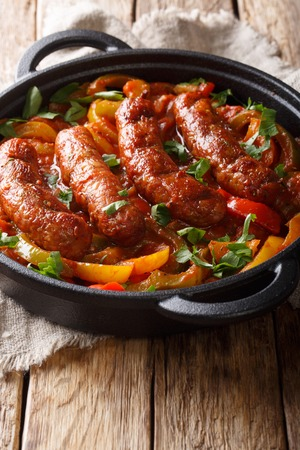 Delicious Italian sausages grilled with bell peppers, onions and tomatoes close-up in a frying pan on the table. vertical Zdjęcie Seryjne