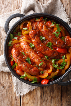 Grilled Italian sausages with bell pepper close-up in a pan on the table. Vertical top view from above