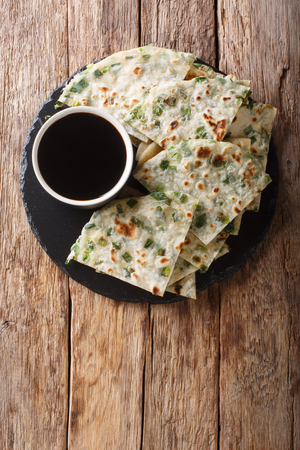 Vegan Scallion Pancakes are a crispy pan-fried Chinese flatbread close-up on a board on the table. Vertical top view from above Фото со стока