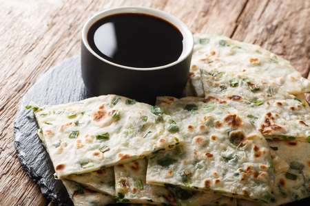 Chewy, flaky, and savory scallion pancakes with sauce close-up on a board on the table. horizontal Фото со стока