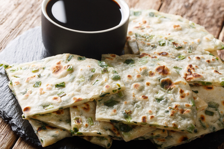 Chinese Scallions pancake also known as green onion pancake or congyoubing  close-up on a board on a table. horizontal