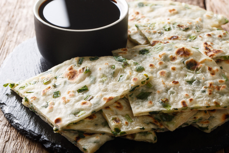 Chinese appetizer fried Scallion pancakes served with sauce close-up on a board on a table. horizontal Фото со стока