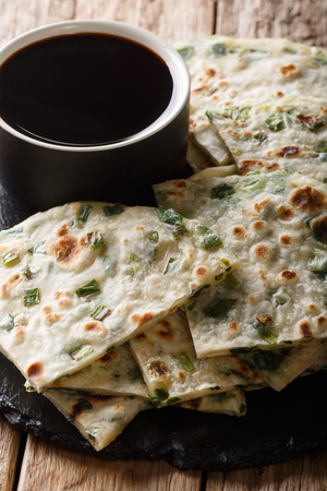 Delicious Chinese vegetarian onion pancakes served with sauce close-up on a board on the table. vertical