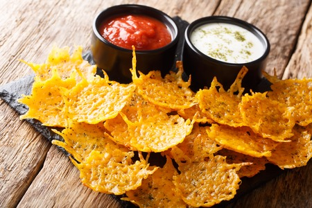 Delicious crispy cheddar cheese chips with herbs with sauces close-up on a board on a table. horizontal Stok Fotoğraf