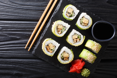 Japanese rolls wrapped in avocado with omelet, sesame and cucumber closeup on a plate on the table. Horizontal top view from above